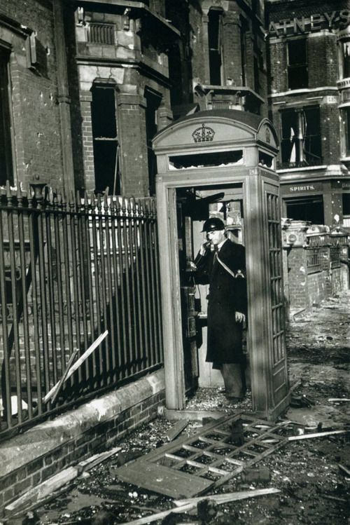 An air-raid warden phones from a shattered booth after a bombing raid. London, 1940. George Rodger