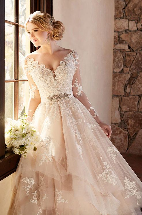 This elegantly crafted designer tulle wedding dress from Essense of Australia features alluring illusion lace sleeves and eye-catching cuts of tulle on its skirt. Essense of Australia, Fall 2016
