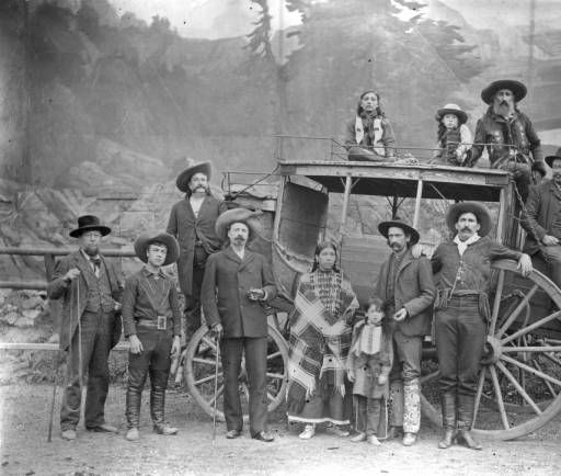 """1889 pic of William Frederick """"Buffalo Bill"""" Cody standing in front of the Deadwood Stagecoach while John Nelson, driver of the stagecoach, sits on the top with 2 of his Sioux children. Julie Keen, treasurer of Buffalo Bill's Wild West Show, sits on the back. Buck Taylor, one of the star cowboys & Bronco Bill, another star, stand in front. A woman & child are next to Bronco Bill. Young Johnny Baker, a big attraction in the show & foster son to Cody, stands between Cody & Fred Matthews."""