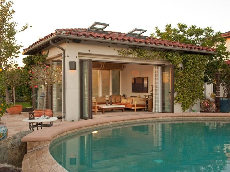 a mediterranean style pool house covered with ivy creates