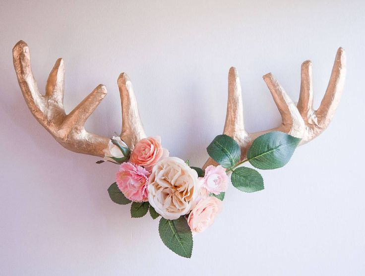 This beauty is taking up space on the other wall in our living room (opposite the chalkboard wall with our family pictures). For some reason I felt that I just HAD to have antlers in our home and after searching good ol' Pinterest I decided I wanted floral antlers. After running around Target Hobby Lobby Joann Fabrics and Michaels my mom and I found a paper mache deer head that was the perfect size. We cut off the antlers spray painted them gold and then hot glued the greenery and flowers…