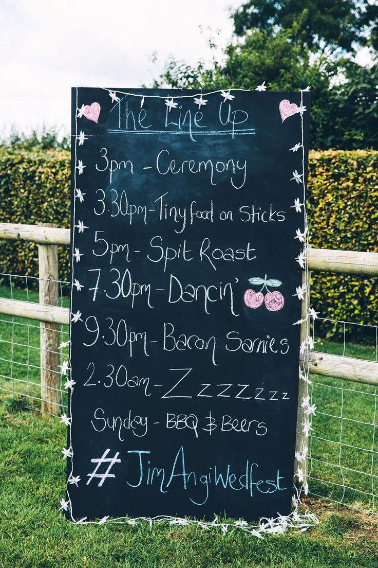 Large chalkboard order of the day sign with twitter & instagram hashtag - Image by Mister Phill Photography - A vintage dress with a bespoke cape for a brightly coloured festival, country fete themed wedding on parent's property with an outdoor ceremony.