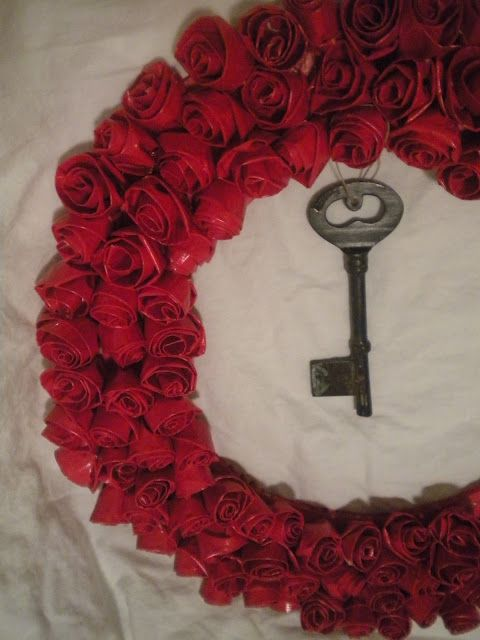 Duct tape wreath--Tear 6 to 8'' strips of red Duct Tape ps...one roll isn't enough, buy 2.Fold the strip 3/4 of the way over so you still have stickiness at the bottom.Fold one edge over. This will be the END of your rosette.Don't fold it all the way to the bottom. You still need the stickiness.Start rolling on the other side. And the simply hot glue the rosettes to the wreath