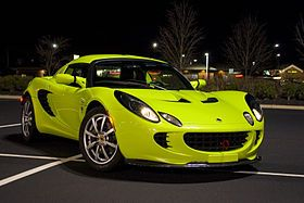 Picture of a 2005 Krypton Green Lotus Elise.  The car is positioned diagonally across parking space markings in an empty parking lot of a shopping mall in Ten Broeck, Kentucky, US. A number of stores are visible in the distant background. It is night and the car is illuminated by a tall overhead lighting post to the left front of the car (not visible within the framed picture) that casts a shadow almost directly under the car, but shifted slightly to the right rear. Numerous reflected ...