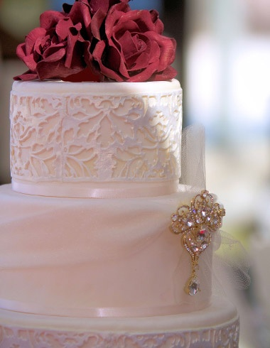 Wedding cake in sugar lace and ivory tulle with rhinestone brooch and deep red roses.