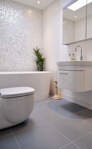 sparkly mosaic wall tiles and large grey floor tiles in contemporary white bathroom. Nice.