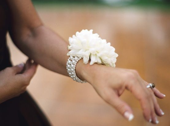 Modern corsage: pearl bracelet with one big bloom.  Corsage for MoB and MoG  I really like this....
