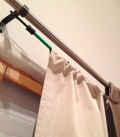 Hang two sets of curtains on one rod using this cool trick. It's simple, just hang your blackout curtains on a bungee cord behind your decorative curtains - no one will see the cord and assembly is a breeze!