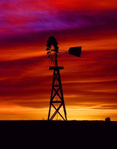 Brilliant colored Sunset and Windmill against a West Texas sky in the Texas Panhandle. c.