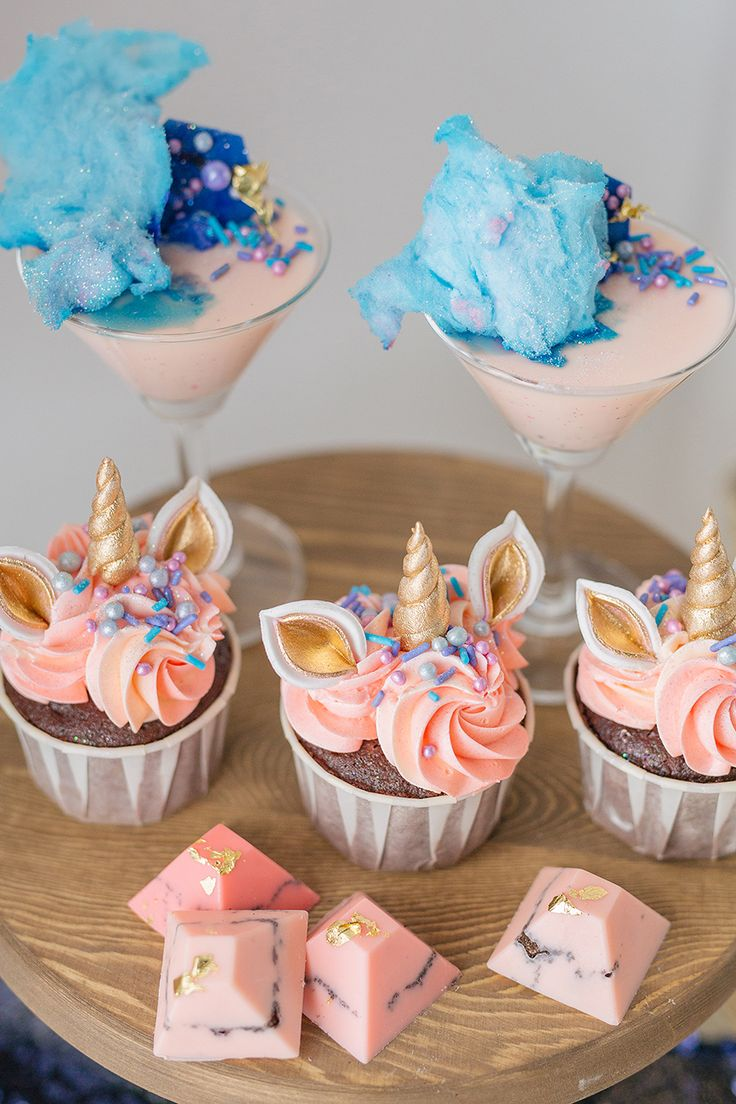 Adorable pink-frosted unicorn cupcakes with golden horns alongside iceberg blue frosting on pink pana cotta and pink chocolate with blue marbling for a beautifully colourful dessert table  // Whimsical cakes, cupcakes, cake pops, pana cotta and macarons which will leave you dreaming of unicorns galloping through galaxies tonight