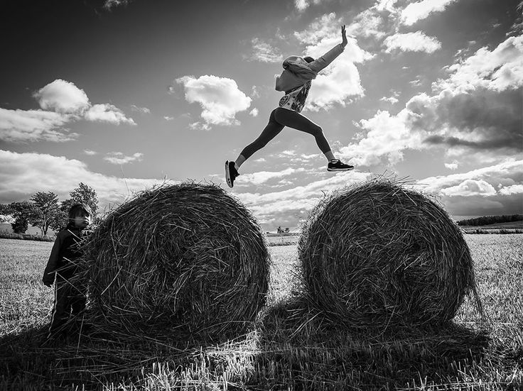 Picture of a girl jumping from one hay bale to another in the Masurian Lake District, Poland