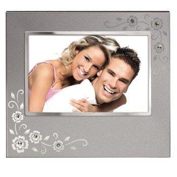 Hama. Portrétový rámeček Phoenix, 10x15 cm, stříbrný. - stříbrný kovový rámeček s květy a třpytivými prvky - pro fotografii formátu 10x15 cm - možnost postavení vertikálně/horizontálně - možnost zavěšení vertikálně/horizontálně - reflexní sklo - materiál: kov  - barva: stříbrná. Foto Dolejš cena 219 Kč.