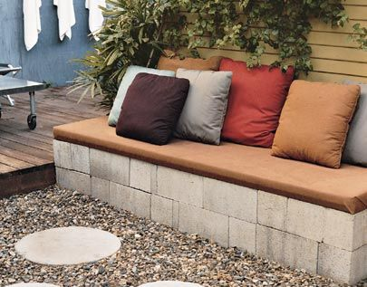 "cinder block bench never looked so inviting! Made from 32 blocks (8x8x16"") alternately laid out to fill an 8'x2' area (covered with 2"" blanket of builders sand) & topped with padded plywood covered in weather resistant fab."