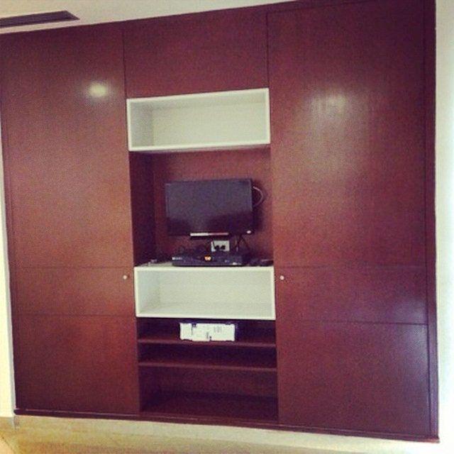 Closet con nicho de TV integrado fabricado en madera de caoba. Excelente opción para espacios pequeños. #grupotricasa #tumejoropcion #excelenciaencarpinteria