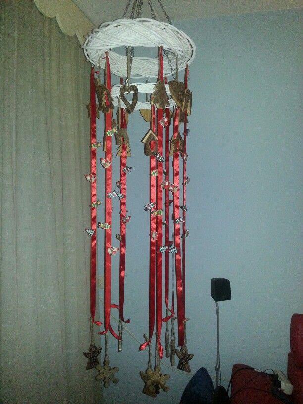 Kaartenkrans. Twee rotan kransen boven elkaar met linten voor kerstkaarten aan te hangen. Verder versiert met houten kerstdeco en kerstwasknijpers voor de kaarten.