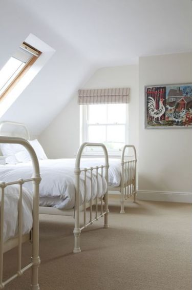 Children's bedroom | The mansard space makes a perfect bedroom for children. Painted iron bed frames reminiscent of a dormitory. Picture by Mark Hearld.