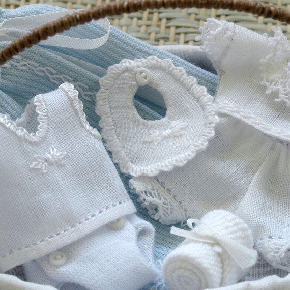 Canastilla de madera y trenzada imitando mimbre. Forrada en tela blanca y tira bordada. Contiene 7 prendas con trabajo de lencería. Bordado y cosido