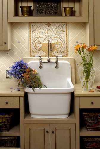 Love this laundry room sink and the beautiful tile work behind it.