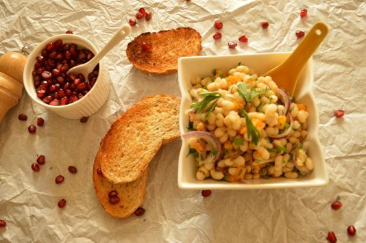 white bean salad with red onion and pomegranate seeds