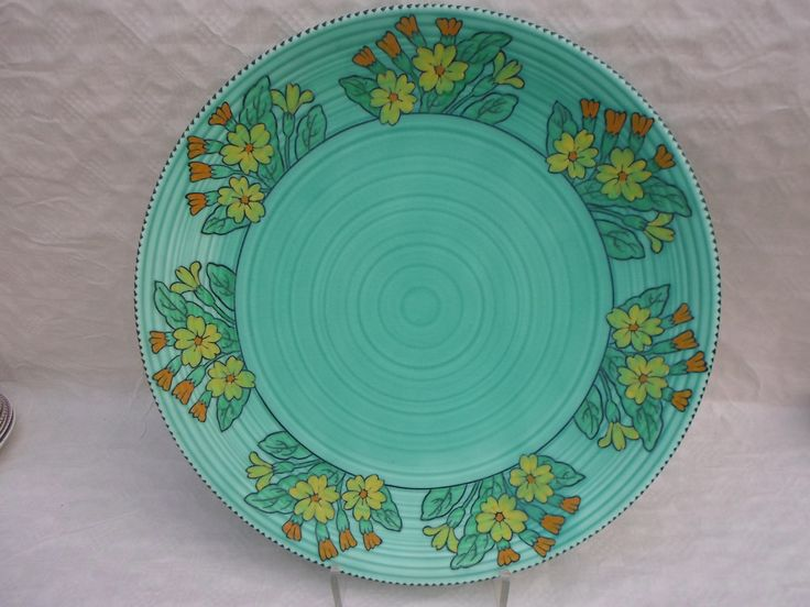 A large 1930s Crown Ducal wall plaque, designed by Charlotte Rhead in the Primula pattern, having a tube-lined decoration of stylized flowers in orange and yellow, on a green glaze ground, printed and tubed marks verso to include a facsimile Rhead signature, 44cm diameter