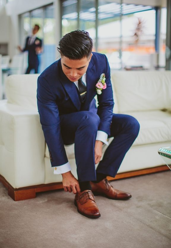 Amazing get-up by Joe Button groom in our custom navy blue three-piece suit. Designed and custom made for the groom who paired it with gold accessories and brown shoes. Perfect! Photography by Gersom Santos Photography