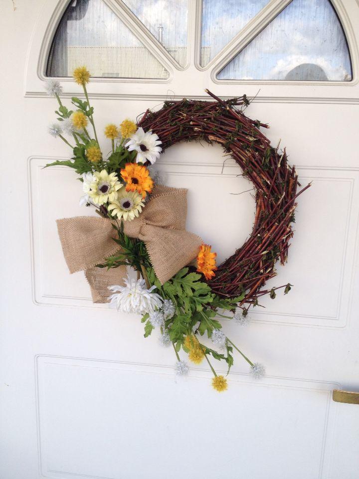 Hjemmelagd dørkrans- en halmkrans, noen kvister fra naboens busk, noen kunstige blomster fra IKEA, ei striesløyfe og en limpistol. Raskt og ganske fint