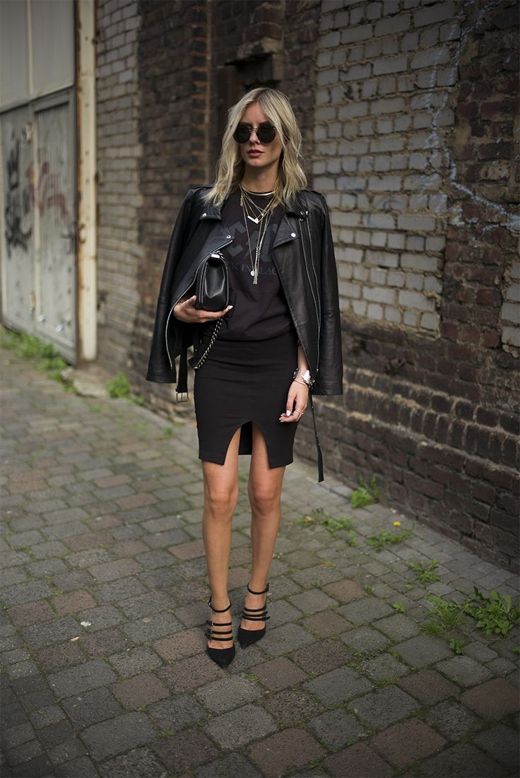 Rocker tee tucked into black pencil skirt. Black pumps. Black leather jacket. Sunglasses, layered necklaces, bracelets, rings, black bag.