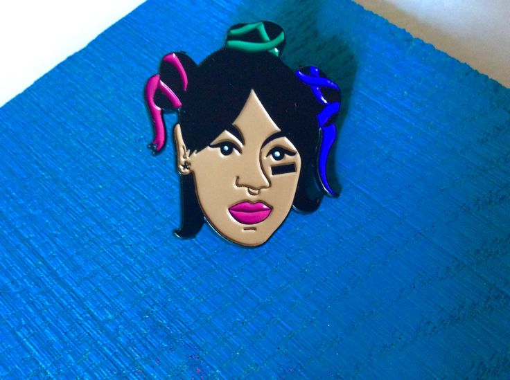 """Represent your girl Left Eye from TLC with this fun soft enamel pin. R.I.P. Size: 1.5"""" Soft rubber clutch backing. Arrives in small poly bag. Includes handmade spray painted backing card. Each one hand numbered."""