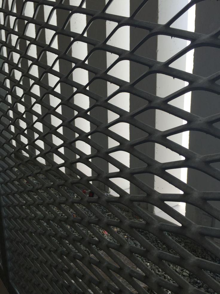 LIJN Hek aan parking. Dit hek bestaat uit diagonale lijnen in beide richtingen. Je kan erdoorheen de achtergrond zien die ook uit vertical lijnen bestaat. De achterste lijnen zijn dikker en de voorste zeer dun, daardoor wordt het niet te druk.