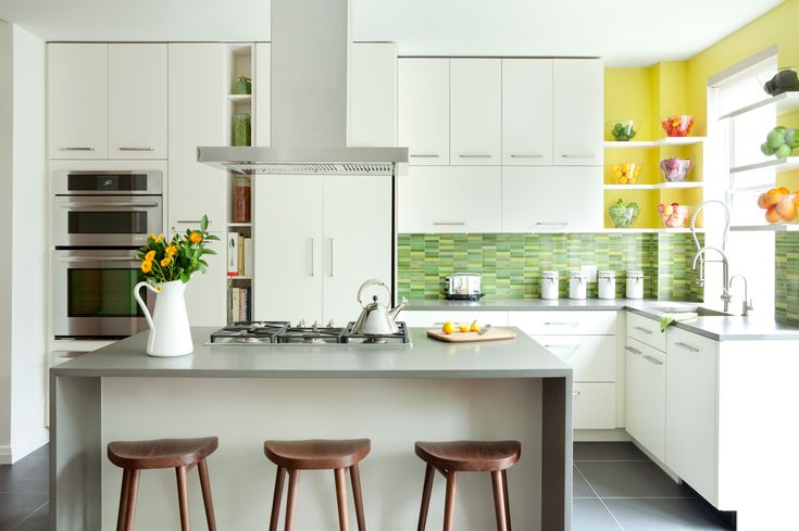 green glass tile is the focal point in the white kitchen, by Fawn Galli designer
