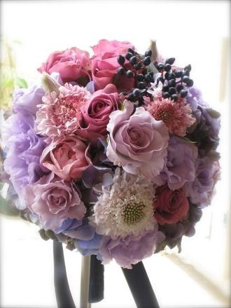 光を含む花びらがふわっと優しいブーケ    淡いパープル、ピンク、ホワイトと、優しい色でまとめたラウンドブーケです。色の優しさに加え、柔らかに咲くバラ、トルコキキョウ、スカビオサの持つ優しいラインに光を含んで、ふわっとした雰囲気に。そこにティナス、黒のサテンリボンを挿し色として加えることで、大人可愛いブーケに仕上がりました。