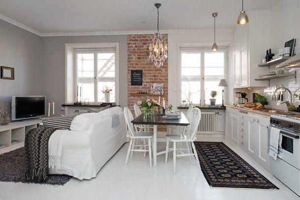 Zdjęcie:   jednopokojowe białe mieszkanie skandynawskie ze ścianą z czerwonej cegły