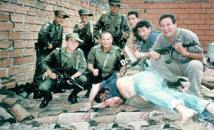 """""""Members of Colonel Martinez's Search Bloc celebrate over Pablo Escobar's body on December 2, 1993, in a photograph taken by DEA agent Steve Murphy. Pablo's death ended a fifteen-month effort that cost hundreds of millions of dollars. It was the deathblow to the Medellín cartel–it became fragmented and the cocaine market soon became dominated by the rival Cali Cartel, until the mid-1990s when its leaders, too, were either killed or captured by the government."""""""