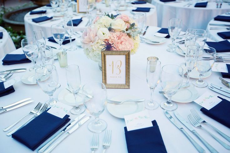 Wedding table decor - blush pink floral centerpiece with hydrangeas, spray roses, and blue thistle, gold frame table number, navy blue pocket napkins