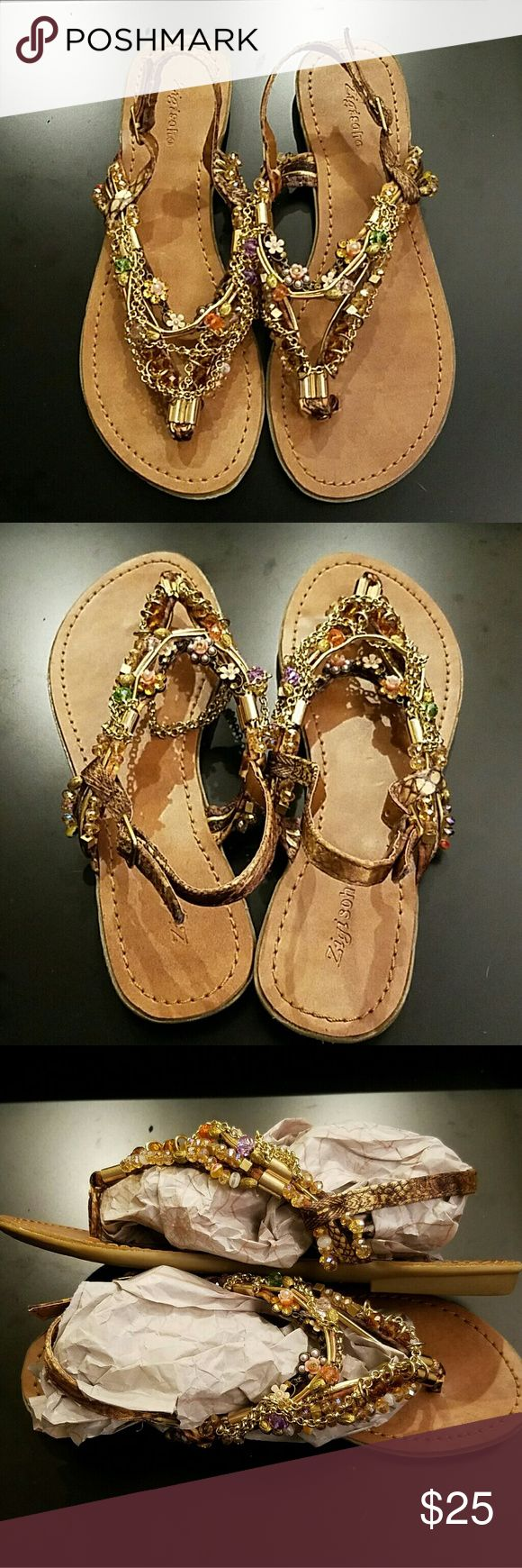 "Gorgeous Zigi Soho ""Precious"" Beaded Sandals Gorgeous Zigi Soho ""Precious"" Beaded Sandals. These feature Gold tone chains, Pink & Orange flowers, multi colored faceted beads, and gold toned hardware. Straps are a brown & gold snake skin print. BEAUTIFUL sandals. They could very easily be dressed up or down. Adjustable ankle strap. No signs of any wear - in LIKE NEW Condition. No box.   ✔offers ✔questions 🚫Trades, 🚫Smoking   🐶Friendly home. Zigi Soho Shoes Sandals"