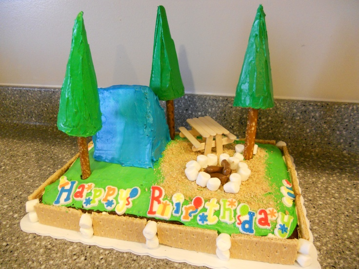 """Camping cake ... last year's birthday creation ... choc cake with marshmallow fluff filling (with gummy worms which the kids LOVED ... """"A worm in the cake! Cool!"""") and graham crackers around the edge. The trees are sugar cones on pretzel rods. The campfire is tootsie rolls and mini marshmallow rocks. The candles are in the fire and when we lit them it sort of melted one of the trees. :/"""
