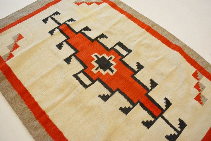 Native American Navajo style wool area rug. This handwoven rug features what is thought to be a Klagetoh design, with a geometric medallion woven in tones of black and red. It features a cream field, with gray-brown and red borders. Southwest design rug.
