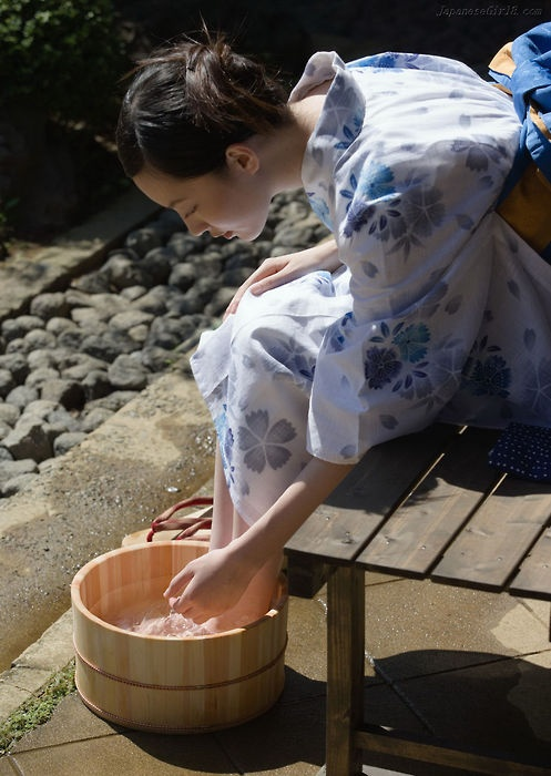 Japanese woman washes feet, possibly prior to a tea ceremony.