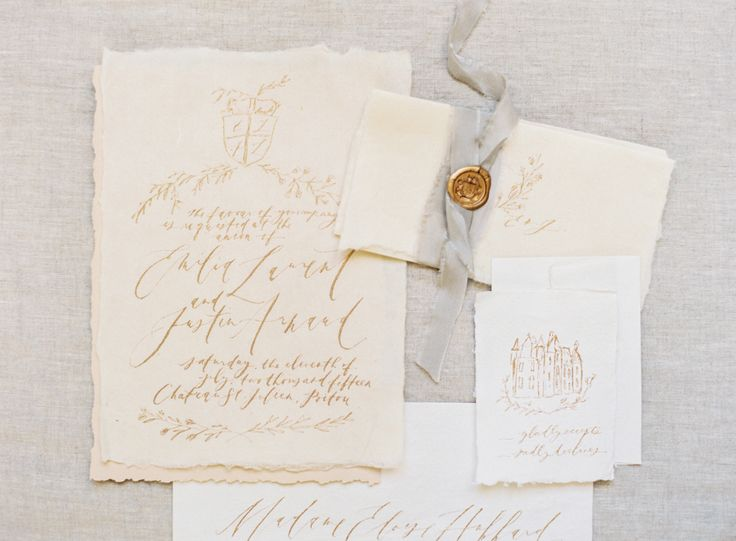 Linen wedding invitation with gold calligraphy and wax embossed grey ribbon.  Photography : Kayla Barker Fine Art Photography Read More on SMP: http://www.stylemepretty.com/2016/04/18/french-chateau-wedding-inspiration-to-sweep-you-off-your-feet/