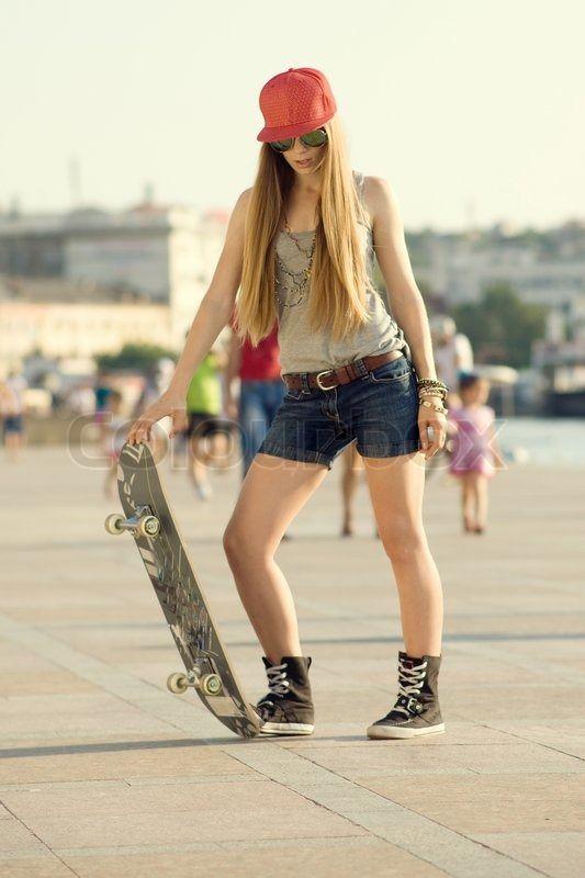Kaufen Sie dieses Hi-res Stock-Foto mit Swag und mutigen Mädchen bereit, Skateboarden Grau T-Shirt, Jeans-Shorts. Einzel-Download kaufen oder bis 90% sp...