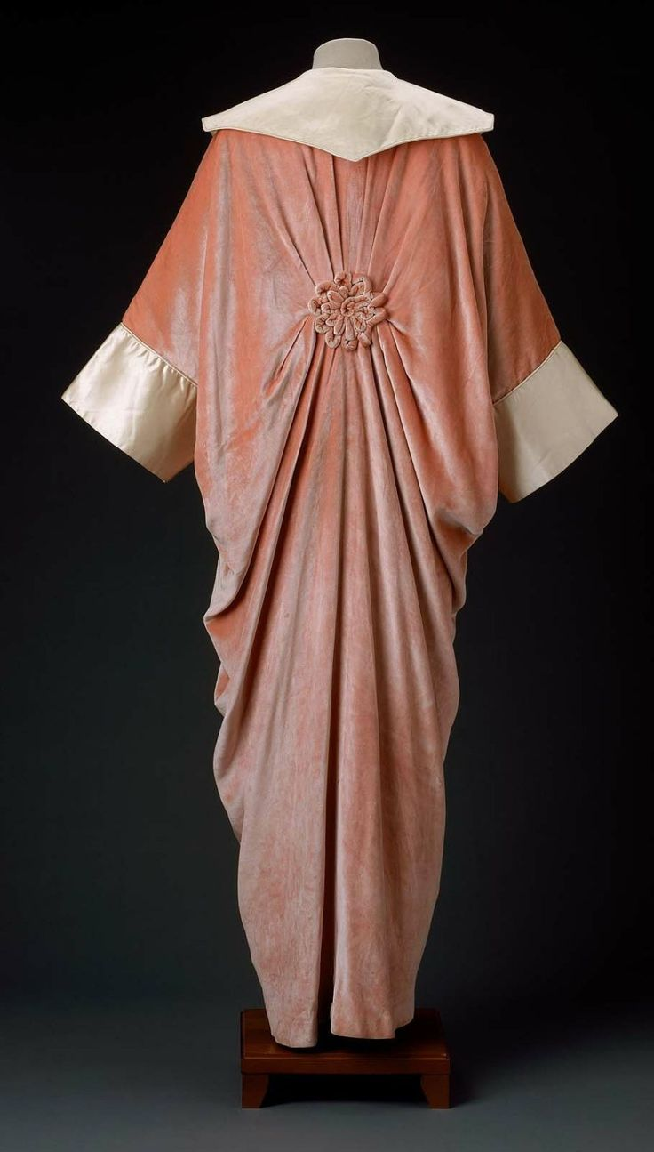 """Coral pink velvet evening coat with cream silk satin collar and cuffs, coral pink silk satin lining. Loose kimono shape gathered in back and secured with pink corded velvet rosette; rosette also at front opening. Label: """"Worth"""", couture stamp (on reverse) no. 24061."""