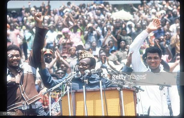 Leader of Zaire Mobutu Sese Seko holds up the arms of boxers George Foreman and Muhammad Ali as the crowd cheers October 1974 in Kinshasa Zaire Ali...