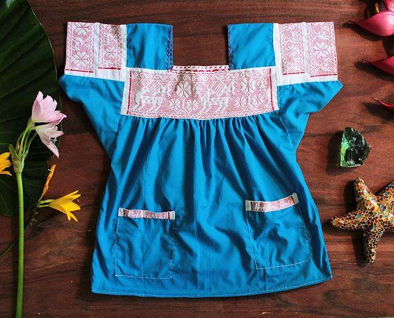 Muy bonita blusa HUICHOL Mexicana 100% artesanal, diseñada y creada por indígenas de la Sierra Mexicana, blusa bordada y hecha a mano. El bordado es un patrón de venados y peyote en color rojo. Esta blusa cuenta con 2 bolsas al frente. Materiales: Popelina: Color azul cielo. Cuadrillé: Color blanco Hilo: Estambre color rojo. Medidas: Sisa: 60 cm. (23.5 pulgadas) Alto: 67 cm. (6.5 pulgadas) Talla: L (Large). ------------ Se recomienda lavar en seco por separado, ó lavar a mano, por s...
