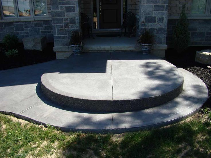 Curved coloured decorative concrete sidewalk and steps add a dramatic entrance to this luxury home.