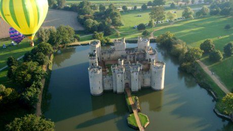 An aeriel view of Bodiam Castle, the moat and grounds with a yellow hot a balloon in view © Brian Williamson