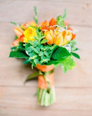 Tulips, gardenia foliage, rosemary, ranunculus, freesia, and oregano tied in orange ribbon