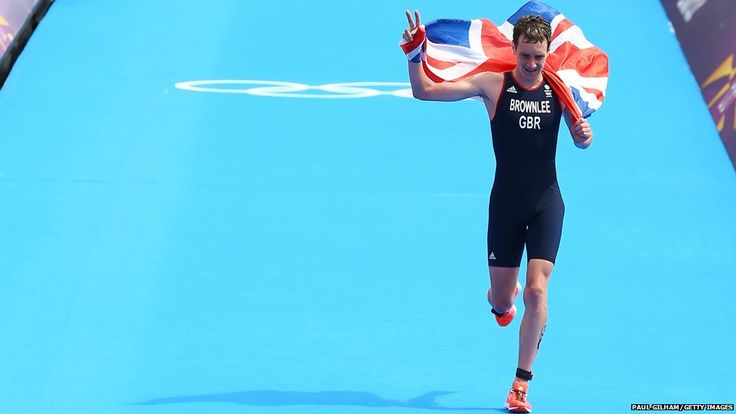 Alistair Brownlee of Great Britain makes a Churchillian V-for-victory sign with his fingers while holding a union jack aloft as he approaches the finish line to win gold during the men's triathlon