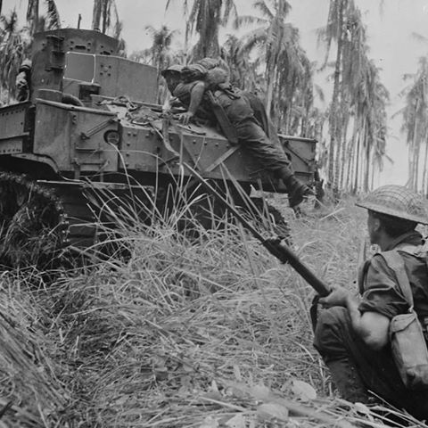 Two Australian soldiers hide behind an M3 Stuart light tank during the battle for the village of Buna, New Guinea. December 1942.