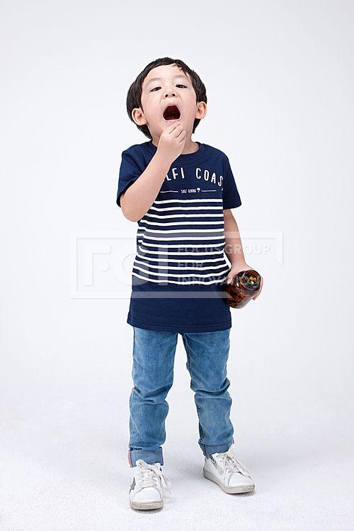 PHO407, 프리진, 사진, 어린이, 사람, PHO407d, 한국인, 동양인, 아시아, 어린아이, 남자, 남자어린이, 소년, 1인, 전신, 앞모습, 서있는, 들고있는, 알약, 건강, 비타민, 약, 먹고있는, 1개, 약병, 잡고있는, 입벌린, pho407 #유토이미지