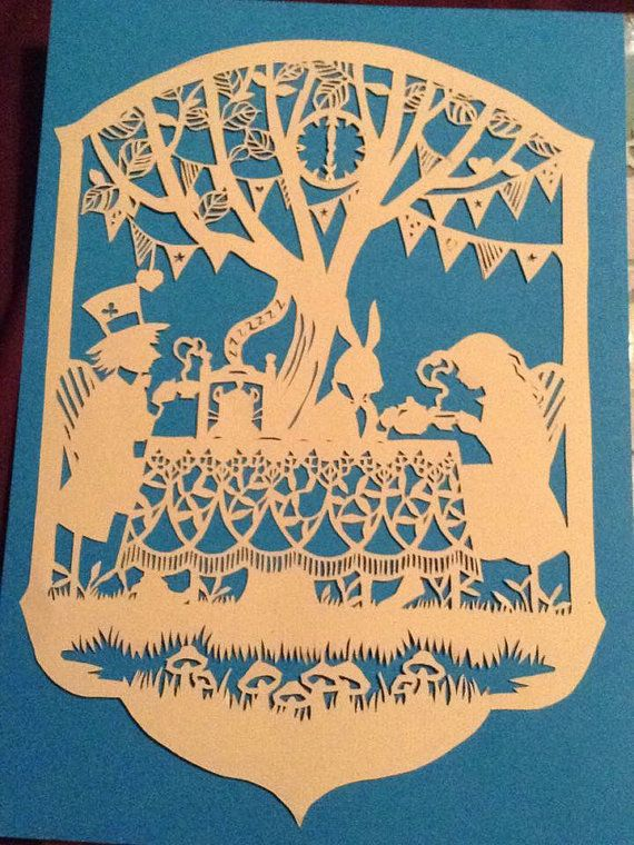 Mad hatters tea party, cut into 120gsm hammered paper and backed with blue. Other options available. Design credit to bramble crafts, handcut by PaperSpace